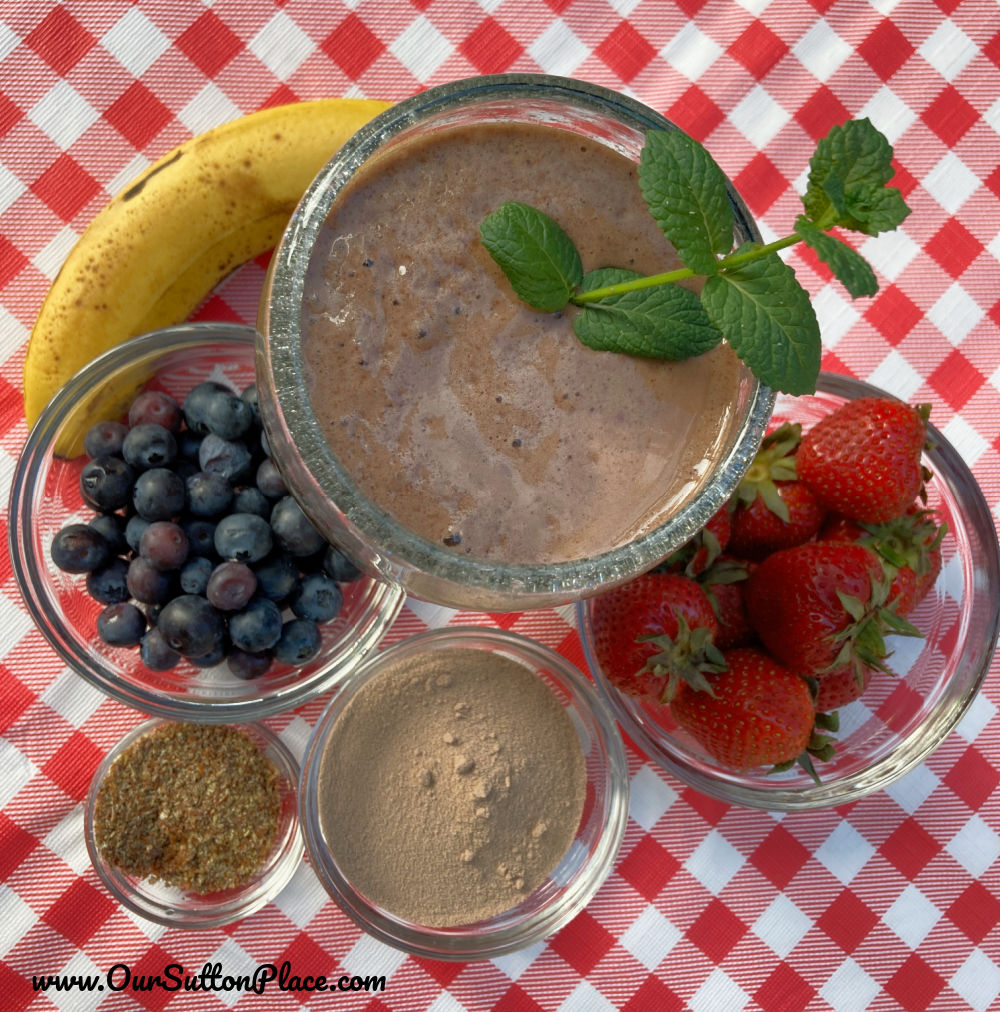 Table with top down view of ingredients including banana , flax seed, protein powder, blueberries, and strawberries