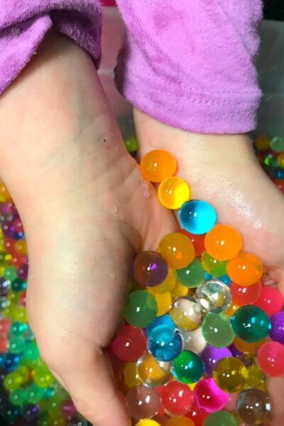 We recently discovered the magical world of Orbeez / water beads and now my kids are obsessed! Learn how to make this super fun Magical Rainbow Water Bead Bin. It's great for kids of all ages. And I have to admit, I thought it was pretty magical as well. #kidsactivities #waterbeads #sensoryactivities