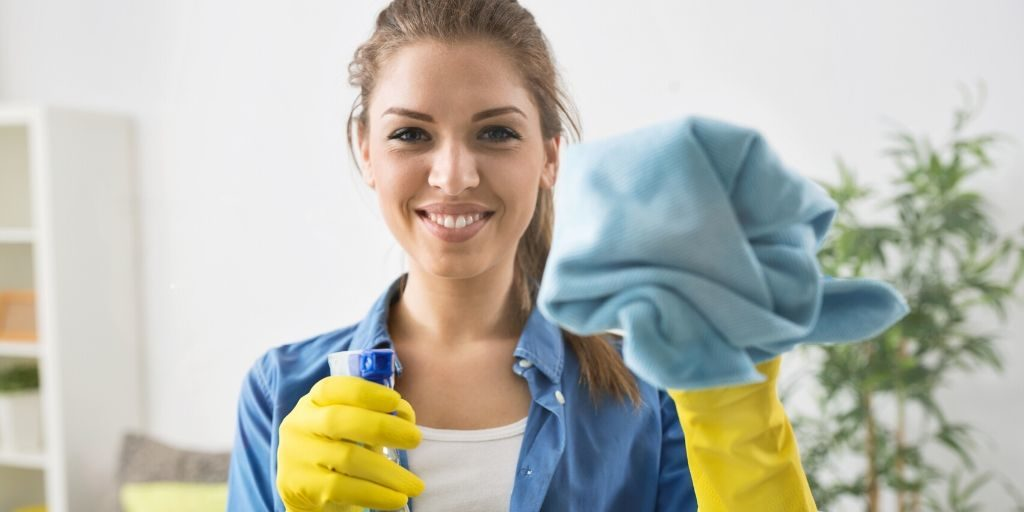 woman using cloth to clean to help eliminate waste