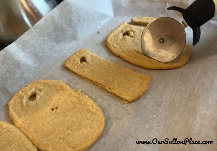 trimming the cookies with pizza cutter