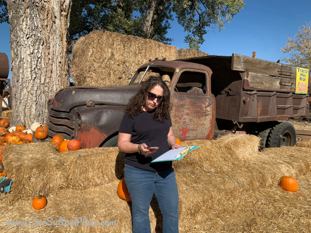 Woman standing looking at her clipboard and cell phone in a pumpkin patch