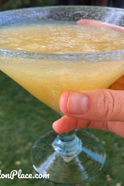 Slushy Pineapple Cosmo Cocktail in glass with grassy background