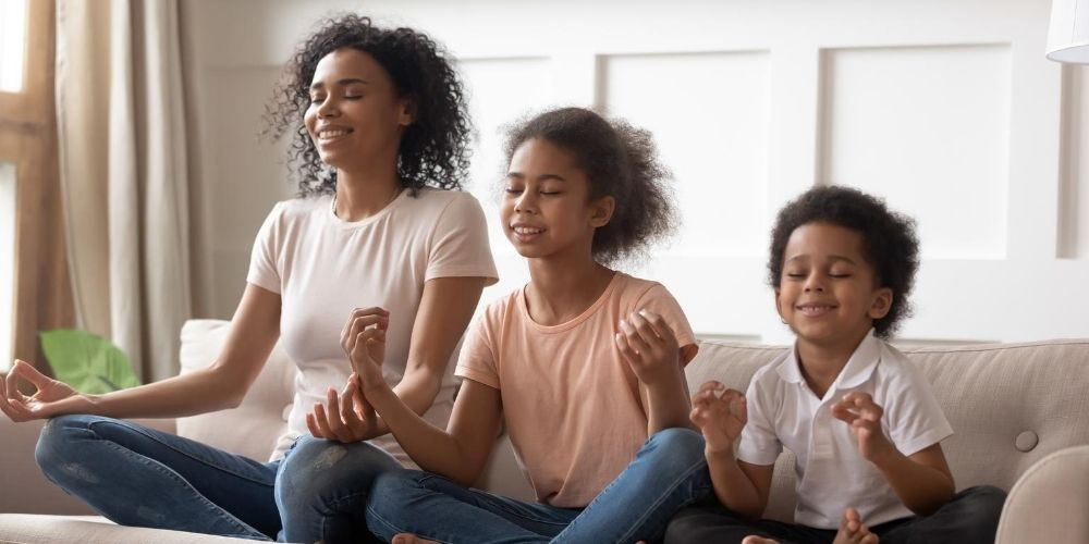 Mom and her kids meditating on the couch