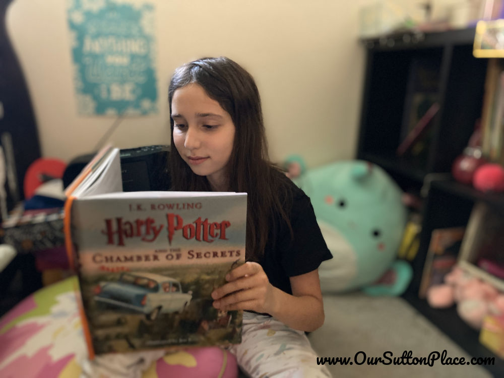 Girl reading a Harry Potter book in her reading nook.