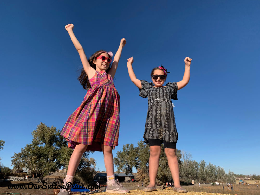 Two girls raising their arms showing they're brave