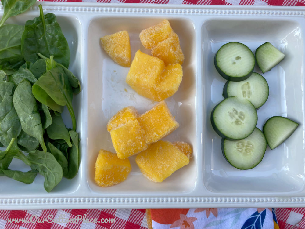 plate of ingredients including spinach, mango and cucumber