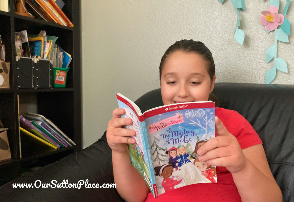 Girl reading an American Girl Welly Wishers book on the couch
