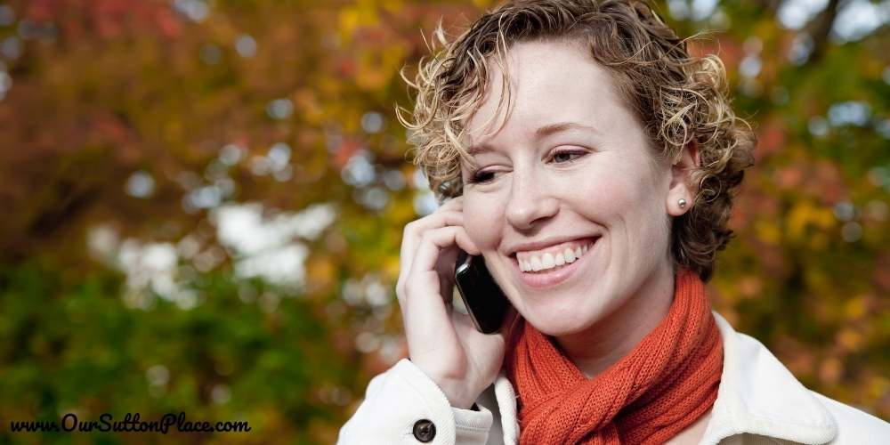 a mom on the phone outside in front of fall leaves
