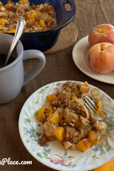 table setting with the French Toast casserole dish, peaches, and a plate full of French toast.