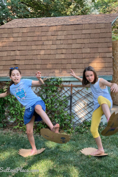 two girls wearing cardboard bigfoot feet