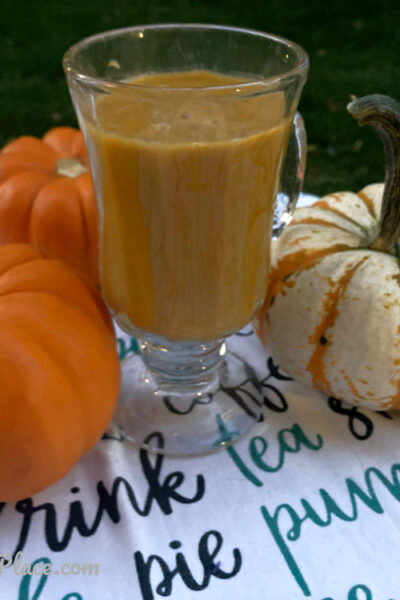 Pumpkin Pie Protein Smoothie outside on a table with some mini pumpkins
