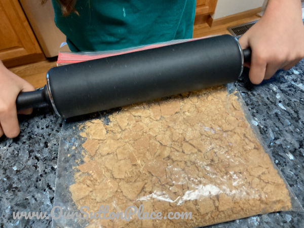 a rolling pin crushing graham crackers in a plastic bag