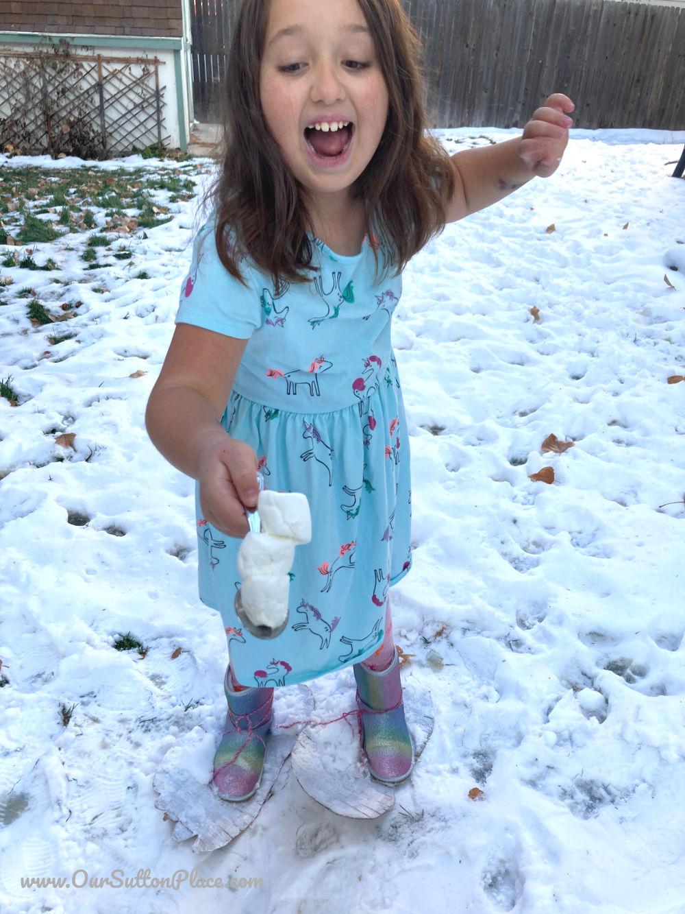 Girl balancing snowman marshmallows wearing Sasquatch feet