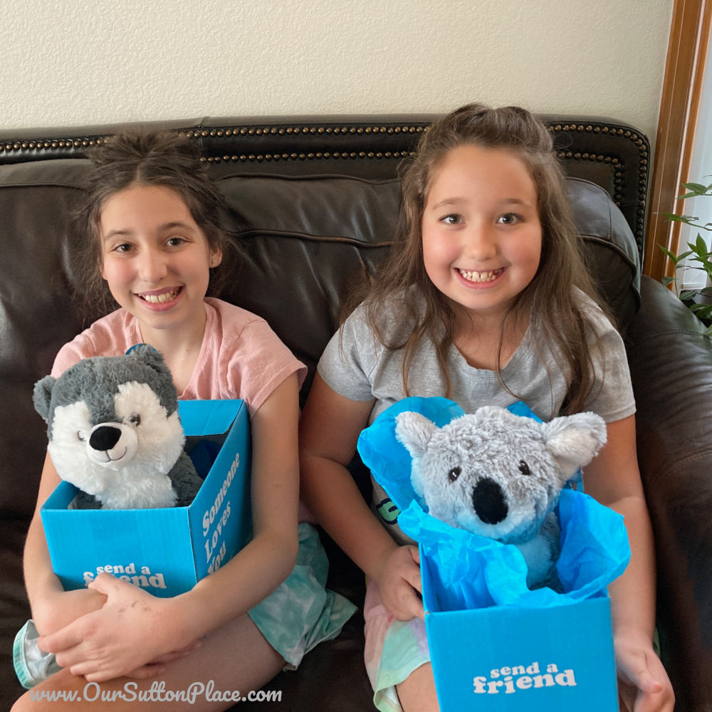 Girls holding 2 Send a Friend plush toys