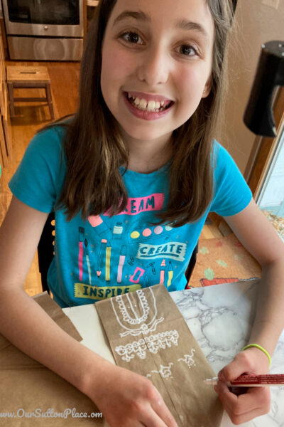 picture of girl creating a Paper Bag Gingerbread house