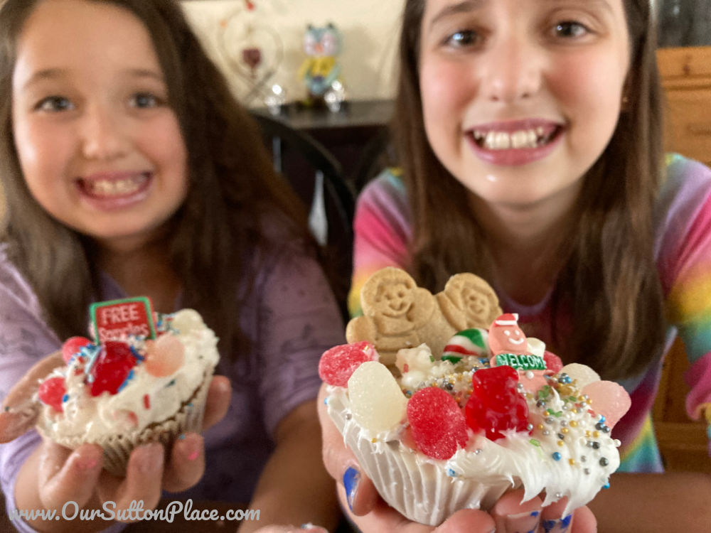 Two girls holding up Gingerbread house cupcakes