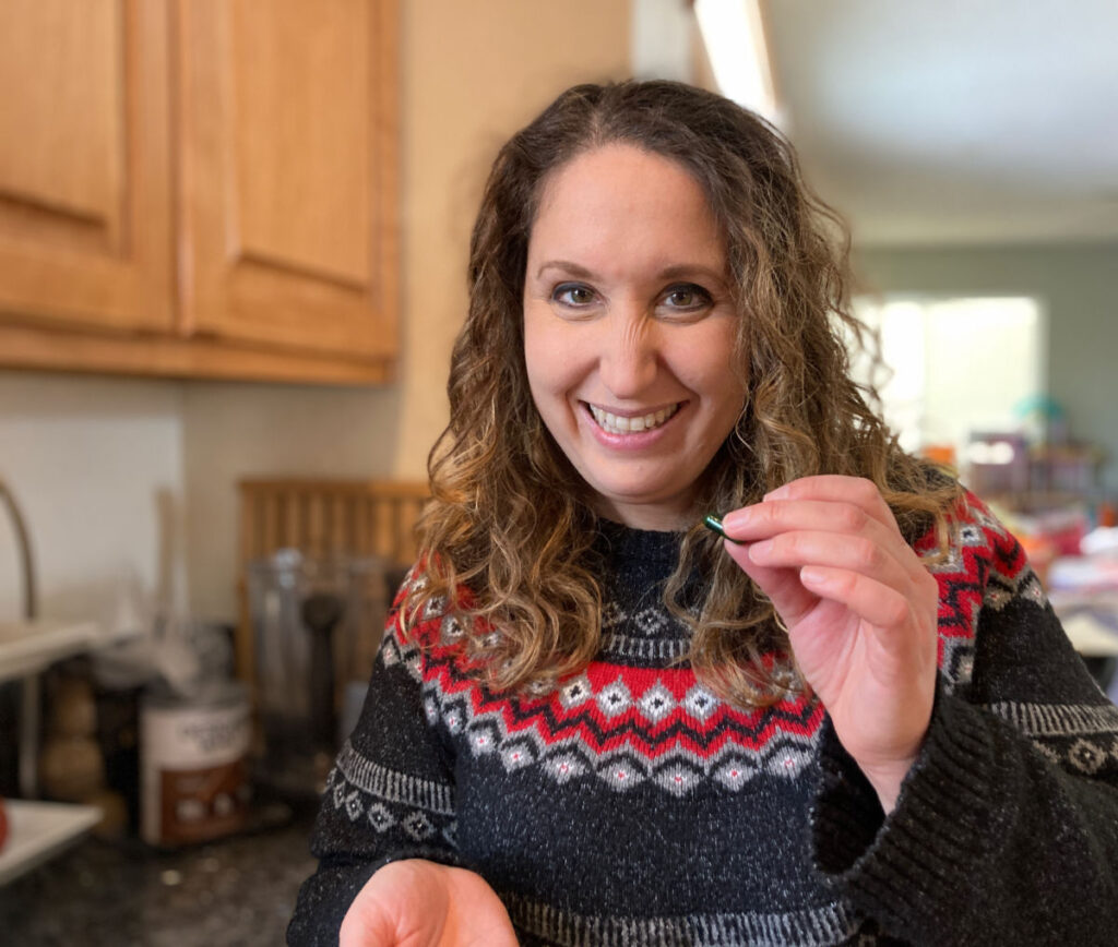 Woman wearing a sweater holding a green Seed Probiotic.