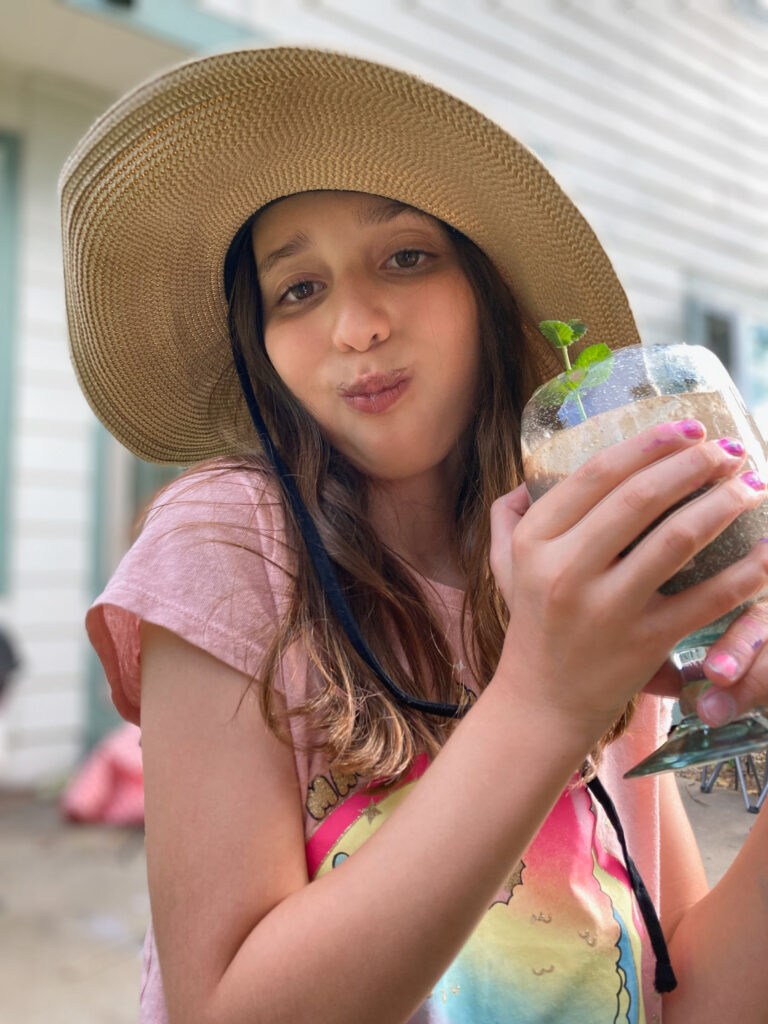 Girl drinking a smoothie wearing straw hat