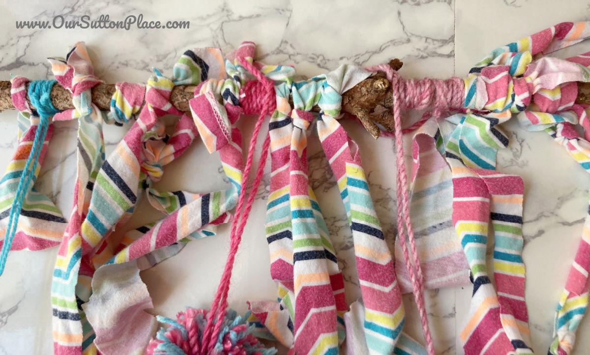 tshirt fabric and pom poms tied around stick