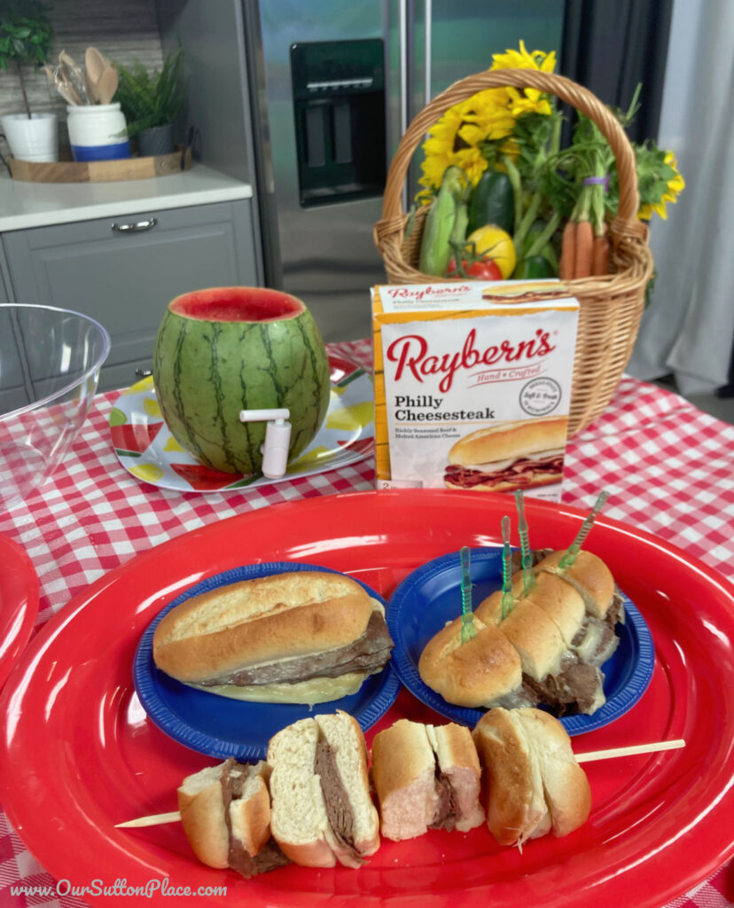 Hero shot of Raybern Philly Cheesesteaks on a table with basket of flowers