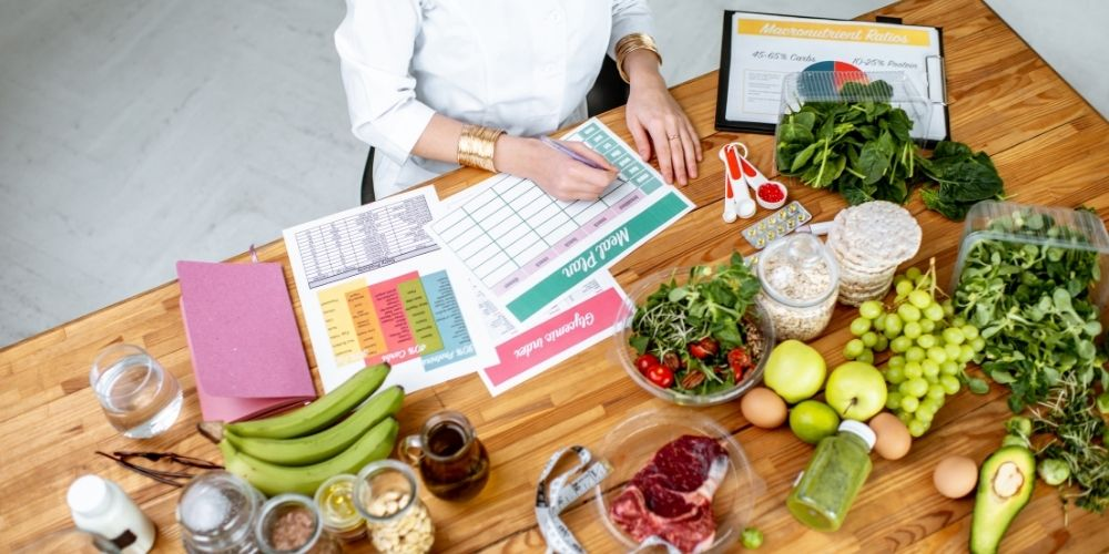 picture of a woman meal planning at a table covered in healthy food